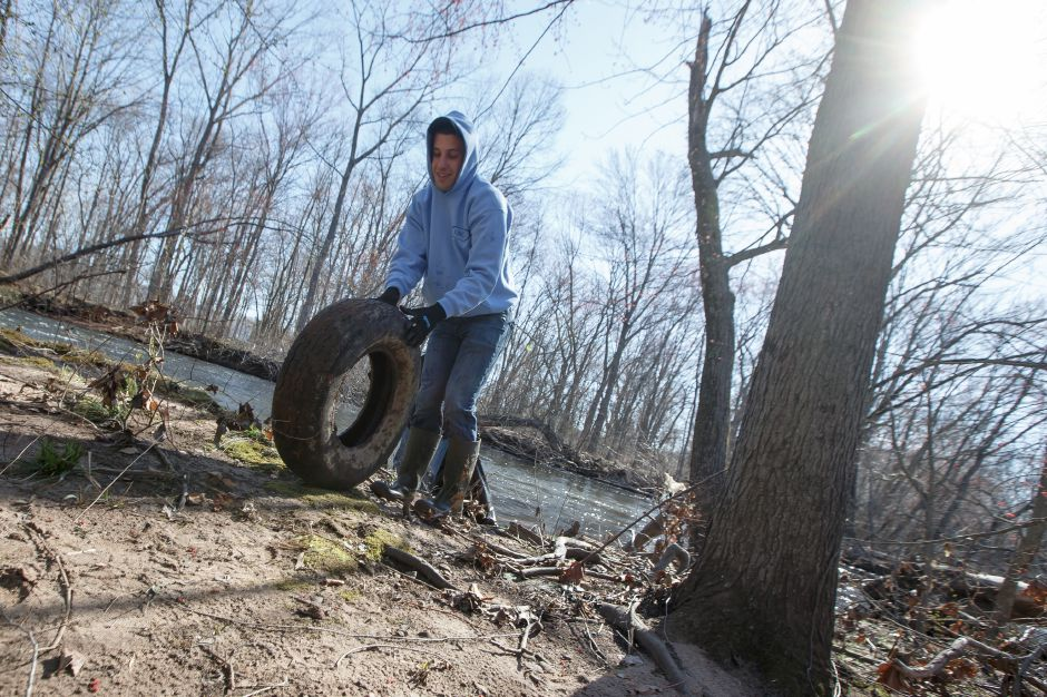 Tim Nielsen of Wallingford rolls a junk tire Saturday during the Quinnipiac River Watershed Association Spring Source to Sound River Cleanup at Westbrook Lobster in Wallingford April 21, 2018 | Justin Weekes / Special to the Record-Journal