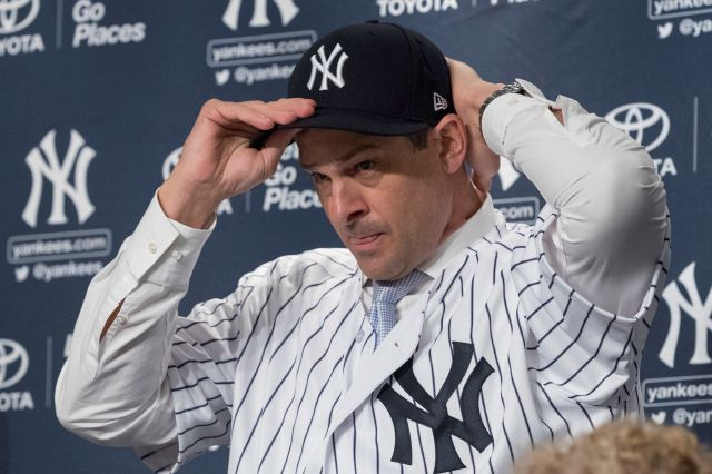 New York Yankees new baseball team manager Aaron Boone puts on a Yankees hat during an introductory news conference Wednesday, Dec. 6, 2017, at Yankee stadium in New York.  (AP Photo/Mary Altaffer)