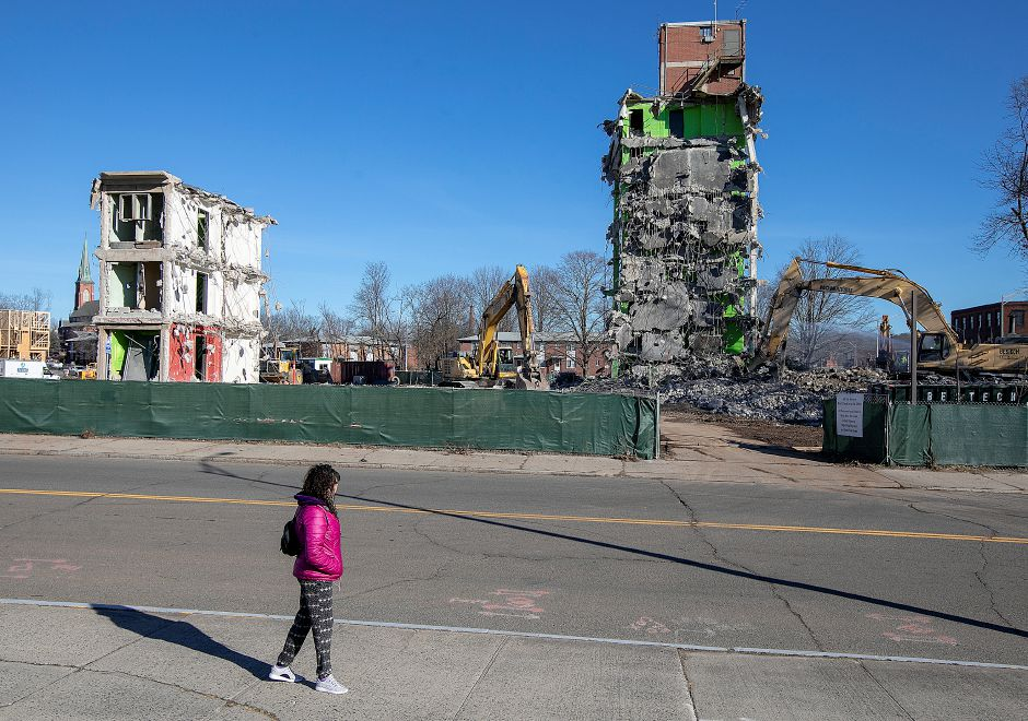 Marisol Montero, of Meriden, watches demolition crews clean up the area around one of the last standing structures of the former Mills Memorial Apartments, Wednesday., Dec. 19, 2018. Montero