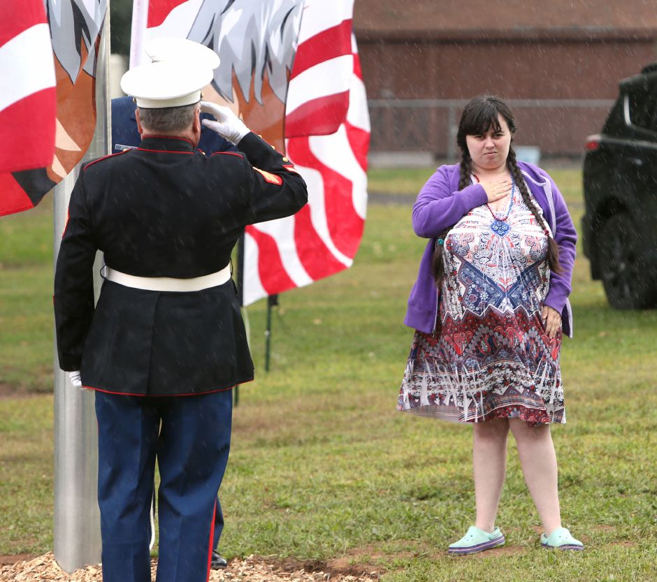 Morgan E. Morenz, of Meriden, puts her hand on her heart in the rain after raising the flag during the celebration of the American Legion's 100th anniversary at the annual American Legion Post 45 All American Picnic in Meriden on Saturday, Sept. 14, 2019. Morenz has raised more than $1,000 for Post 45 through the sales of her artwork. Emily J. Tilley, special to the Record-Journal.