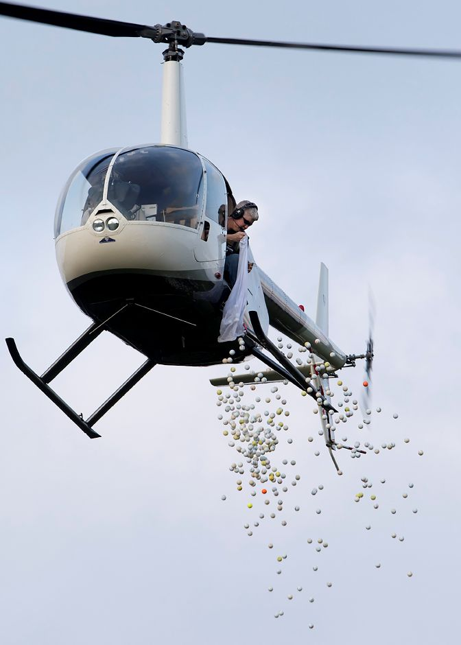 Dozens of golf balls are dropped from a helicopter to a flag on the 18th fairway during the Quinnipiac Chamber Golf Classic at The Farms Country Club in Wallingford on Aug. 22. Dave Zajac, Record-Journal
