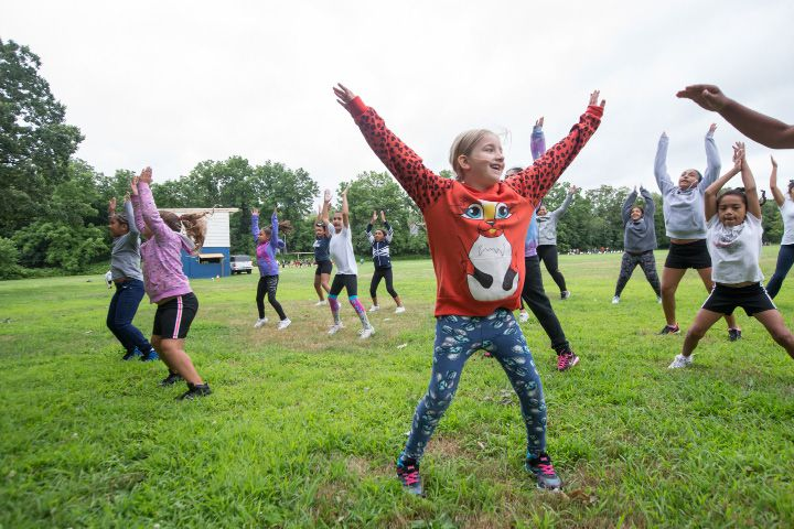 Izabella Bish, 7, of Meriden, does jumping jacks with the Raiders cheer squad Monday during the Meriden Raiders youth football opening day at Washington Park in Meriden Jul. 24, 2017 | Justin Weekes / For the Record-Journal