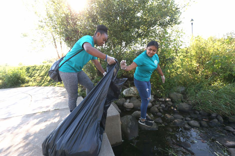 Danika Smith, a Platt High School sophomore, holds a trash bag open for Laura Gonzalez, also a sophomore, as they pull trash from the river in the Meriden Green during the annual Community Cleanup Day on Saturday, Sept. 21, 2019. Emily J. Tilley, special to the Record-Journal.