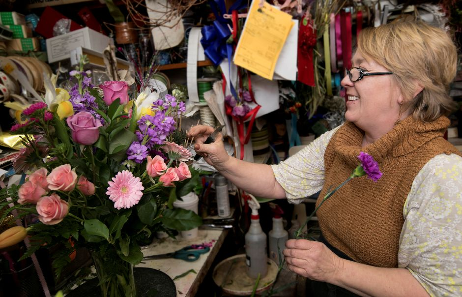 Above: Nina Glinski, owner of Barnes House of Flowers, Inc. in Wallingford, designs a floral arrangement Tuesday for a Valentine's Day customer. Below: Glinski carries a dozen pastel roses to the refrigerator. Dave Zajac, Record-Journal