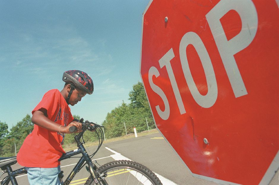 RJ file photo - Ryan Hatcher applies his brakes at a mock intersetion while learning safety tips at the annual Bike Rodeo at Cytec in Wallingford, Aug. 1998.