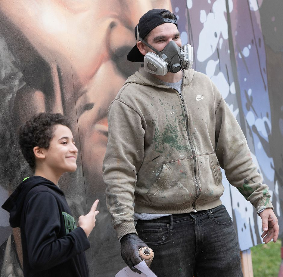 "Eight-grade student Gian Ortiz, 13, poses for a photo with global graffiti artist ""ARCY,"" of North Haven, who spray painted a portrait of Abraham Lincoln on an 8-foot-by-12-foot canvas outside Lincoln Middle School in Meriden, Mon., Dec. 3, 2018. ARCY is known for large scale art he creates all over the world, and for organizations like Major League Baseball, Disney and the National Parks Service. Dave Zajac, Record-Journal"