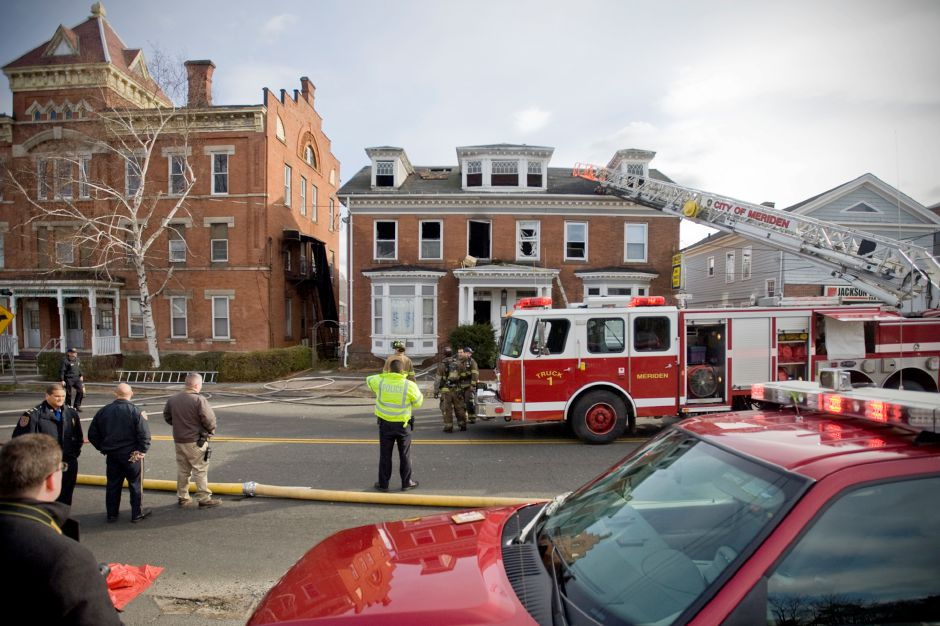 Meriden Fire Fighters vent the roof and extinguish the remaining flames of a multi-family home on Broad Street in Meriden near the corner of East Main Street Tuesday, December 7, 2010. One badly burned man found on the second floor by fire fighters was rushed from the scene in an ambulance. (Johnathon Henninger/ Record-Journal)