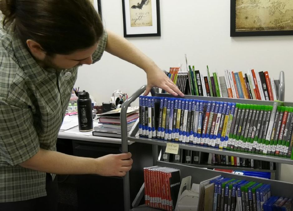 Max Spurr, Creative Technologies Librarian, arranges new video games that will be available for patrons to check out at Wallingford Public Library, 200 North Main St., Wallingford. | Ashley Kus, Record-Journal