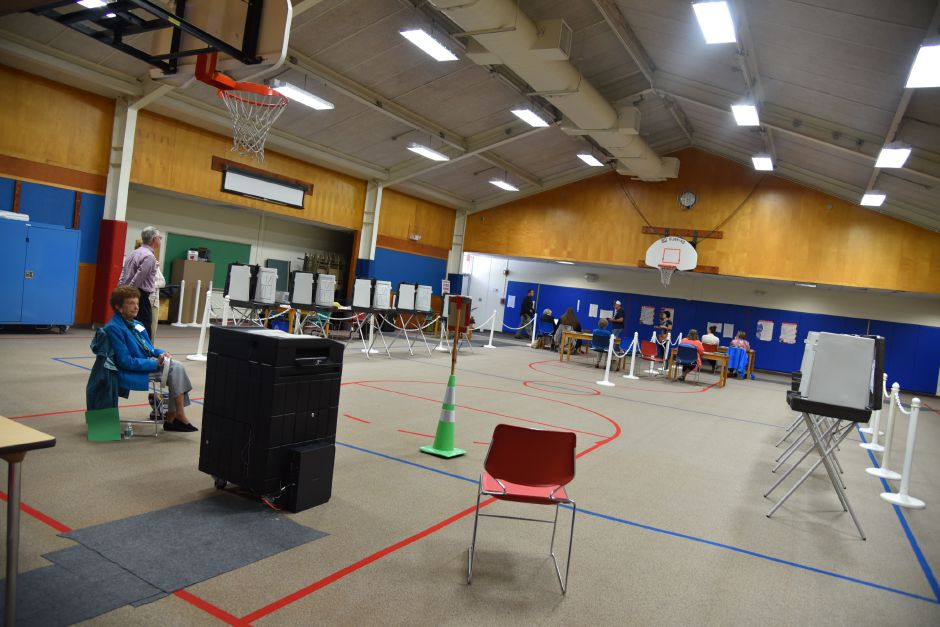 Volunteers man near-empty stalls at the former Korn School building, where voting on Regional School District 13