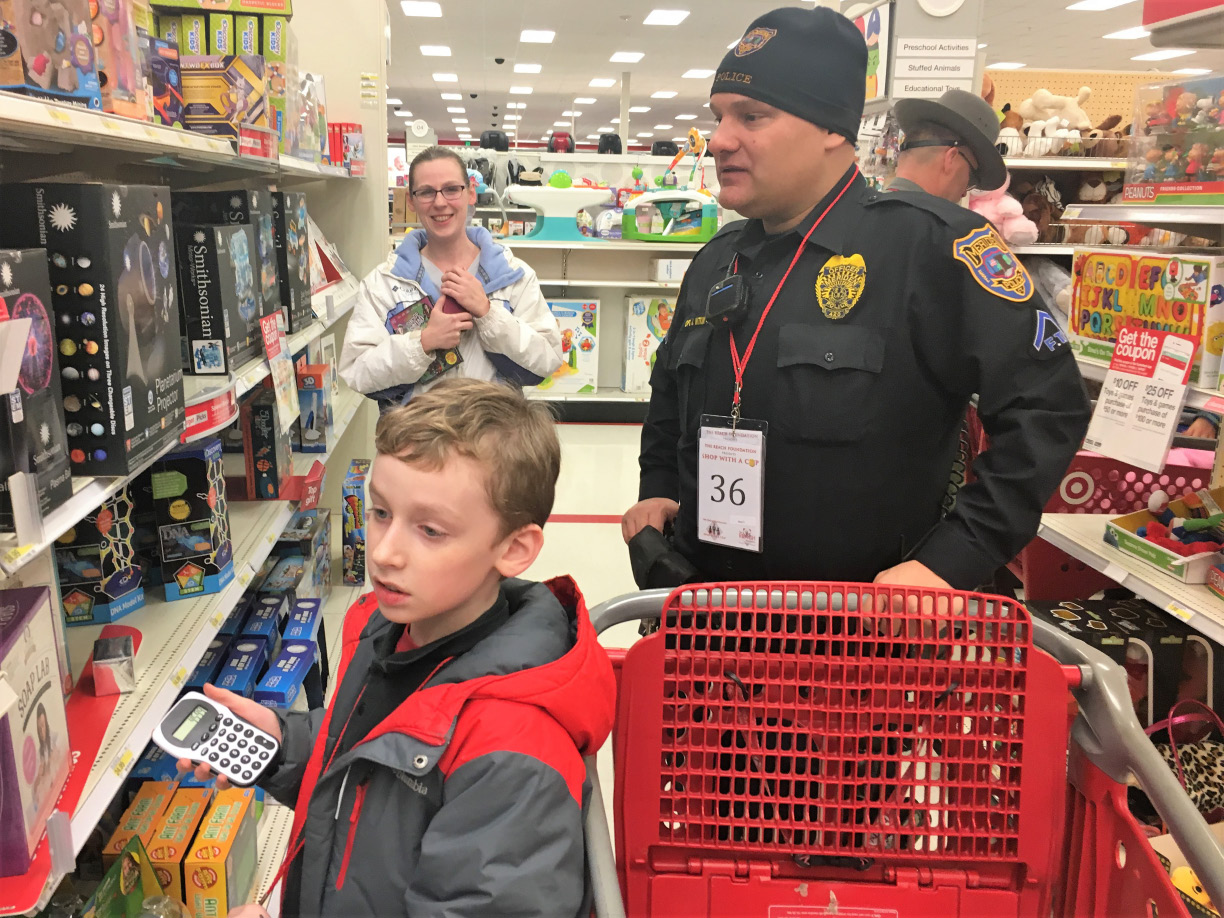Meriden Police Officer Jeff Witkin helps Joshua Duperry, 10, choose holiday gifts while Duperry