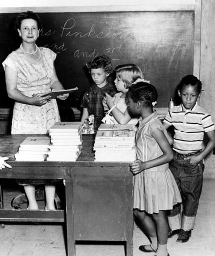 Mrs. Pinkston enrolls 2nd and 3rd graders at the newly integrated classes at a school in Springer, Okla., Aug. 29, 1958.  Getting ready to receive supplies are, left to right, Linda Smith, 8; Karita Ellis, 8; Eva Lois Wilson, 7, and Donald James Herndon, 7.  (AP Photo)