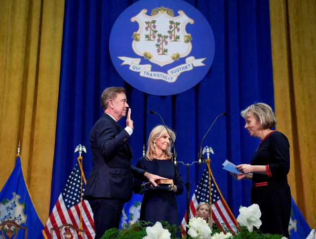 Connecticut Gov. Ned Lamont, left, takes the oath of office administered by former Chief Justice Chase T. Rogers, as wife Annie, center, looks on, Wednesday, Jan. 9, 2019, inside the William A. O