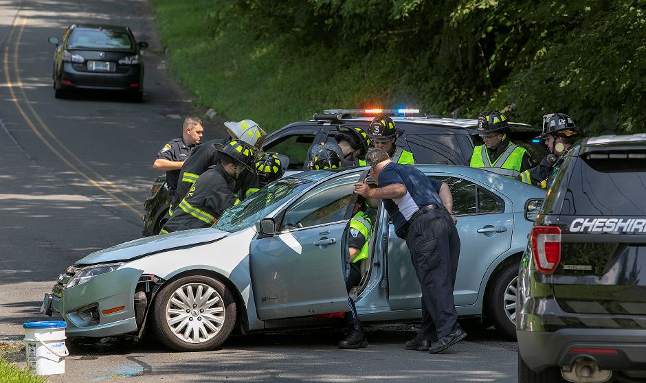 Cheshire firefighters work to extricate a woman from the passenger side of a vehicle that struck a utility pole on Cook Hill Road near Corliss Lane, Friday afternoon, August 10, 2018. Minor injuries were reported. Dave Zajac, Record-Journal