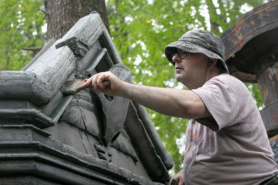 Jonathan Gerolami, set builder/actor, of Branford, brushes paint on an elaborate cemetery scene he created as preparations continues for this year