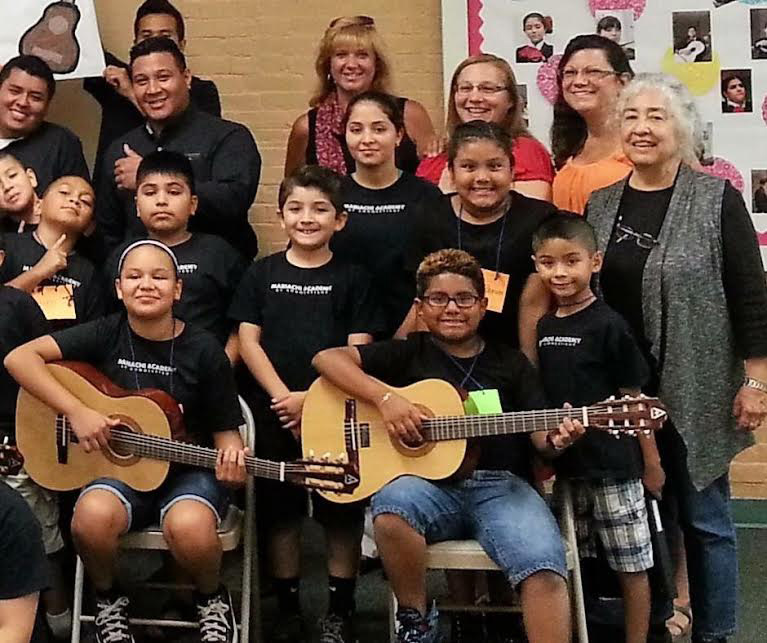 FILE PHOTO - Wallingford Community Women president, Cynthia Parent; vice-president, Jennifer Flood-Frechette; and membership chair ,Donna O'Keefe, present guitars to students at the Spanish Community of Wallingford in 2014.