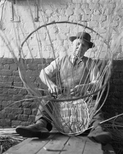 Thomas T. Mullen, makes a large washing basket in his village workshop, in Wickham, Suffolk, Oct. 25, 1959. Thomas has been making baskets for 50 years in his workshop which was founded by his father. (AP Photo/Staff/Smart)