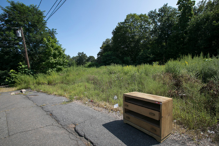 Discarded furniture left near a vacant lot on Edgewood Street off the Chamberlain Highway in Meriden, Friday, August 25, 2017. A development group is requesting a zone change to allow a senior apartment building to be constructed at the location.   | Dave Zajac, Record-Journal