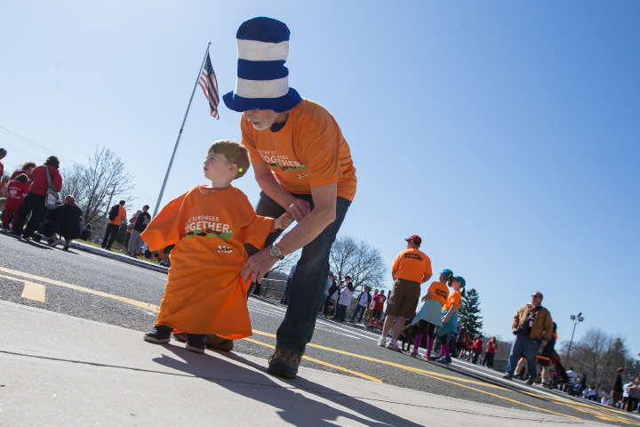 Brian Donohue of Southington helps his grandson Alex Connelly 1 of Avon with his shirt Sunday during the Walk MS held at Cheshire High School in Cheshire Apr. 17, 2016 | Justin Weekes / For the Record-Journal