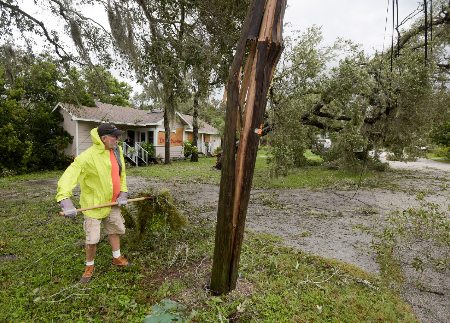 Joe Veciana clears debris from his front yard near a broken power pole after Hurricane Irma, Monday, Sept. 11, 2017, in Palm Harbor, Fla. (Chris Urso/Tampa Bay Times via AP)