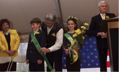 Meriden City Counciler Mike Rohde fastens the sash on the Dafffodil Festival honor escort, Tom Joseph, an 8th grader at St. Mary
