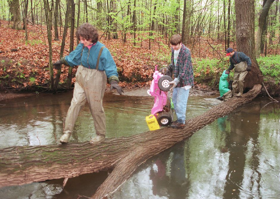 RJ file photo - JoAnn Moran, left, of Cheshire, treads lightly on a fallen tree truck in the Quinnipiac River in Southington during the river cleanup sponsored by the United Earth Fund of Connecticut, May 8, 1999.
