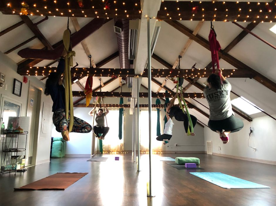 Yoga students partake in aerial yoga using silk hammocks at RaMa LuNa in Middletown. |Kristen Dearborn, Special to the Record-Journal