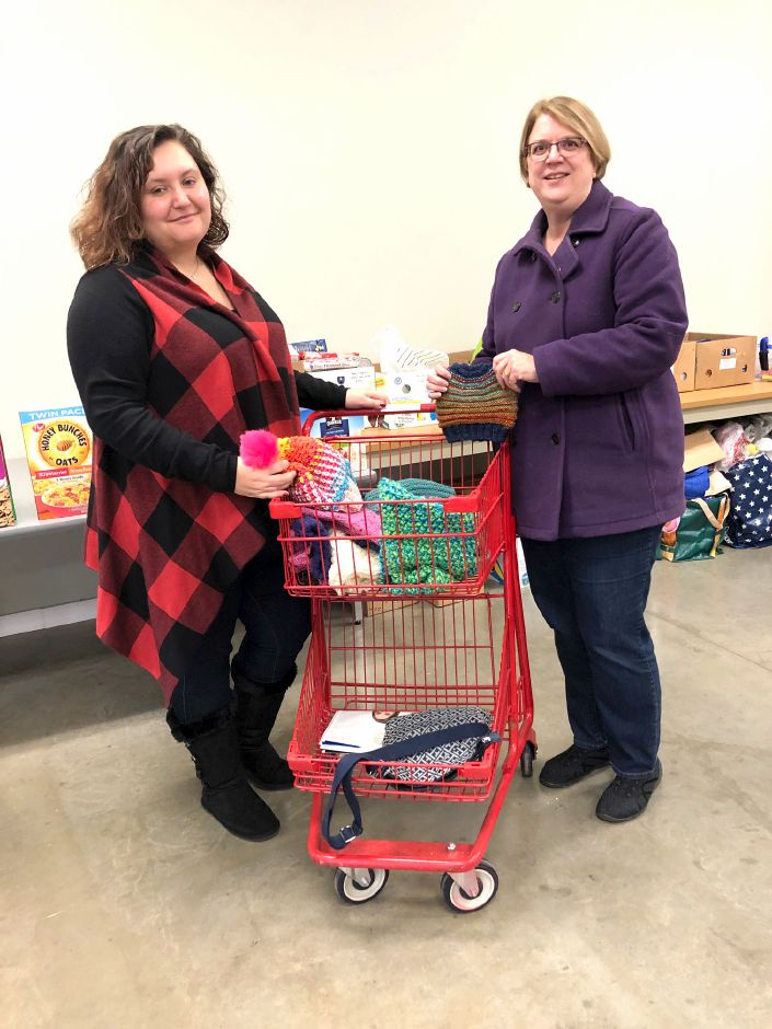Cheshire Community Food Pantry Executive Director April Duquette accepts hand knit items from Rotarian Sally Cabrera.