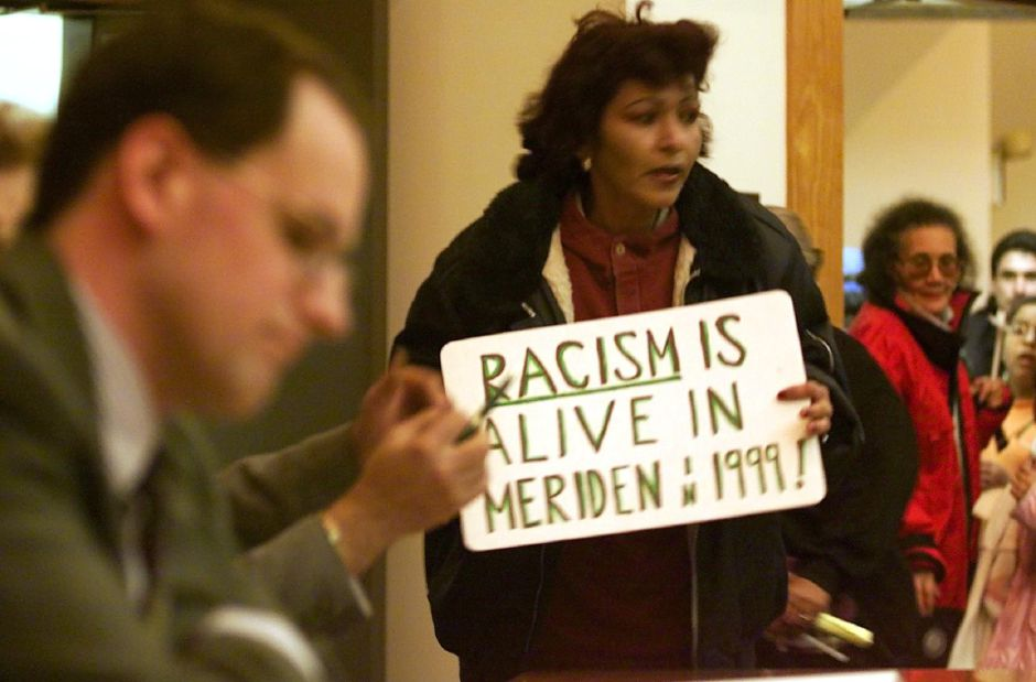 As MHA head Michael Quinn (left) sits quietly with other committee members who were holding a meeting, , Mills resident Marta Curbelo (with sign) makes her case to save the Mills Oct. 25, 1999.