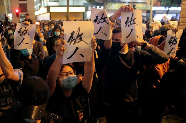 "Protesters hold placards baring the words ""Release People"", shout slogan as they gather near the Polytechnic University in Hong Kong, Monday, Nov. 25, 2019. Hong Kong"