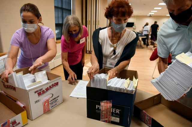 Volunteers sort mail-in ballots on Primary Day, Tuesday, Aug. 11, 2020, in Glastonbury, Conn. (AP Photo/Jessica Hill)