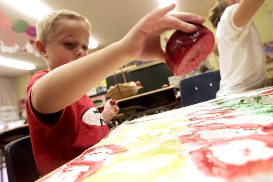 Patrick Bussett is dipping an apple in colored paint and then pressing a print with it onto paper Oct. 5, 2000. Patrick is in first grade at Plantsville Elementary School. The students are learning all about apples through math, reading, tasting, and art.
