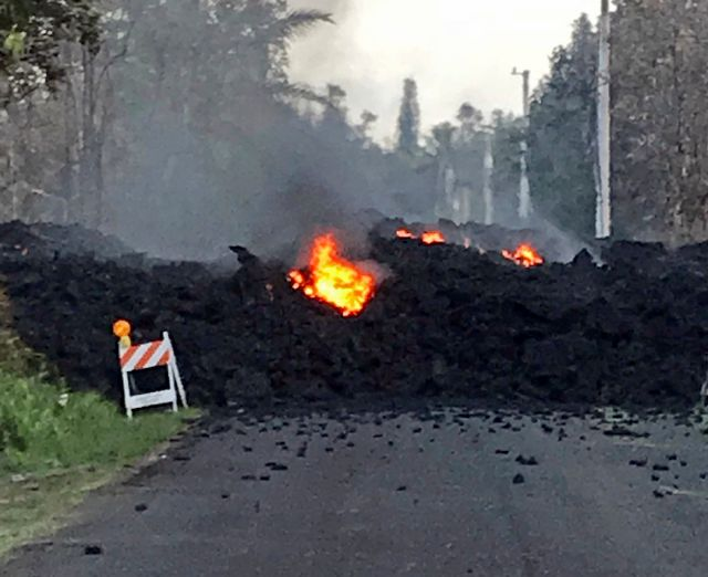 This photo provided by Hawaii Electric Light shows lava flowing over Mohala Street in the Leilani Estates area near Pahoa on the Big Island of Hawaii Friday, May 4, 2018. Nearly 1,500 people have fled from their homes after Hawaii