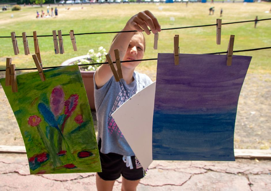 Camper Greta Koscuk, 10, hangs one her paintings up to dry during Art Camp at the Meriden YMCA's Mountain Mist Day Camp on Friday.