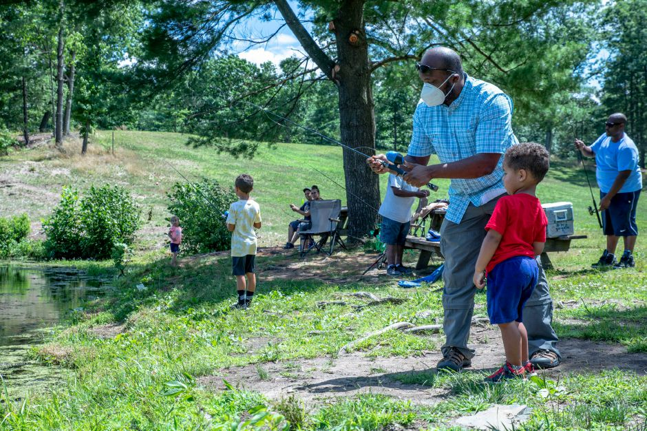 Terryl Dozier shows his nephew Kian Dozier how to fish at Wharton Brook State Park in North Haven, Connecticut on July 12, 2020. Even with sunny and warm weather, visitors remained sparse on Sunday as the Coronavirus pandemic remains a concern. | Devin Leith-Yessian/Record-Journal