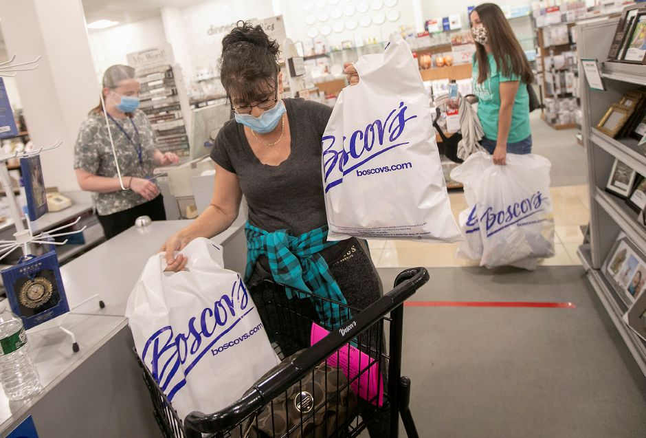 Denise Bachand, of Newington, gathers her merchandise at the checkout counter after shopping at Boscov's at the Westfield Meriden mall, Thurs., May 21, 2020. Boscov's department store reopened at 11 a.m. with reduced hours and new safety precautions. Dave Zajac, Record-Journal