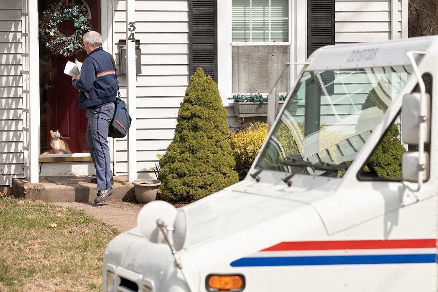 A USPS carrier delivers mail to a residence on Baldwin Avenue in Meriden on Wednesday. Dave Zajac, Record-Journal