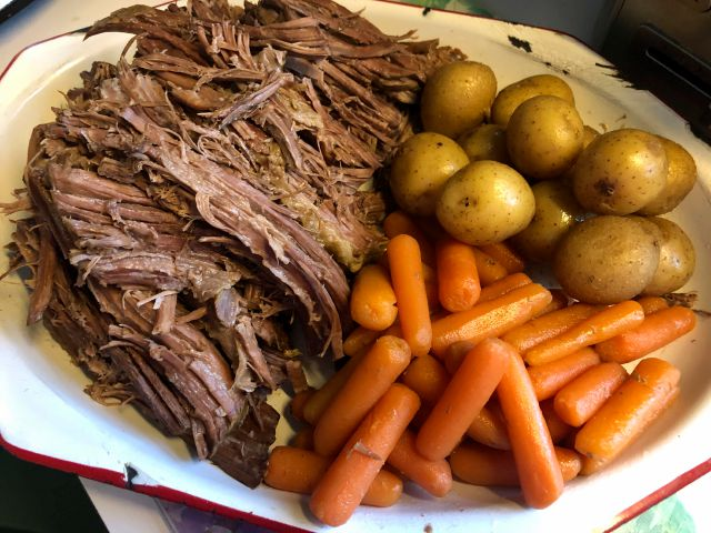 This image released by Kim Bierly shows a pot roast dinner with carrots and potatoes, made in a slow cooker. Before the coronavirus emerged, Bierly often worked late at her office and then met her husband for a quick dinner at one of the restaurants in their central Pennsylvania neighborhood. Now working from home, she