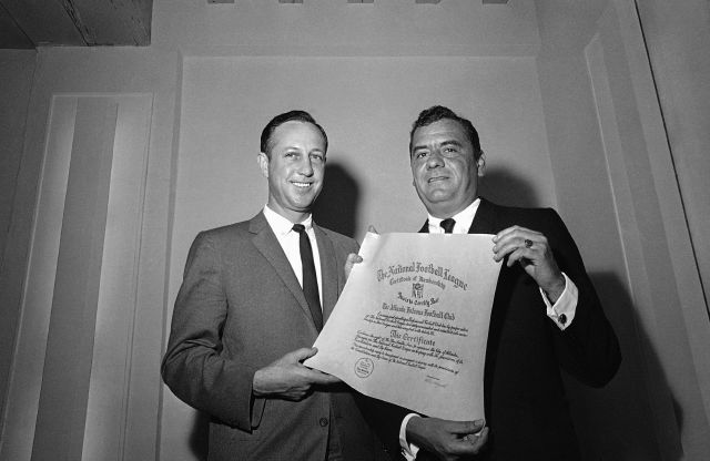 FILE - In this Feb. 15, 1966, file photo, NFL football commissioner Pete Rozelle, left, presents a certificate of membership to Rankin Smith, owner of the Atlanta Falcons football team, in Palm Beach, Fla. To help the 1966 merger agreement meet antitrust concerns in Congress, Rozelle promised that an NFL team already lined up in Atlanta and an AFL team in Miami could stay in those cities. (AP Photo/File)