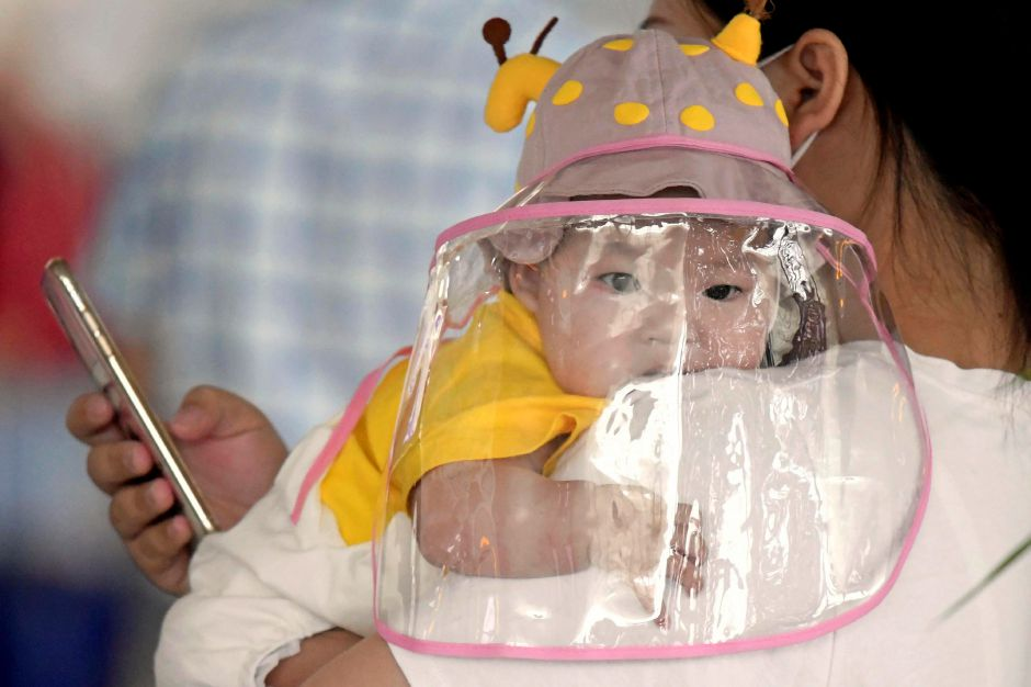 A baby with a face shield waits to board a plane at an airport in Wuhan, central China