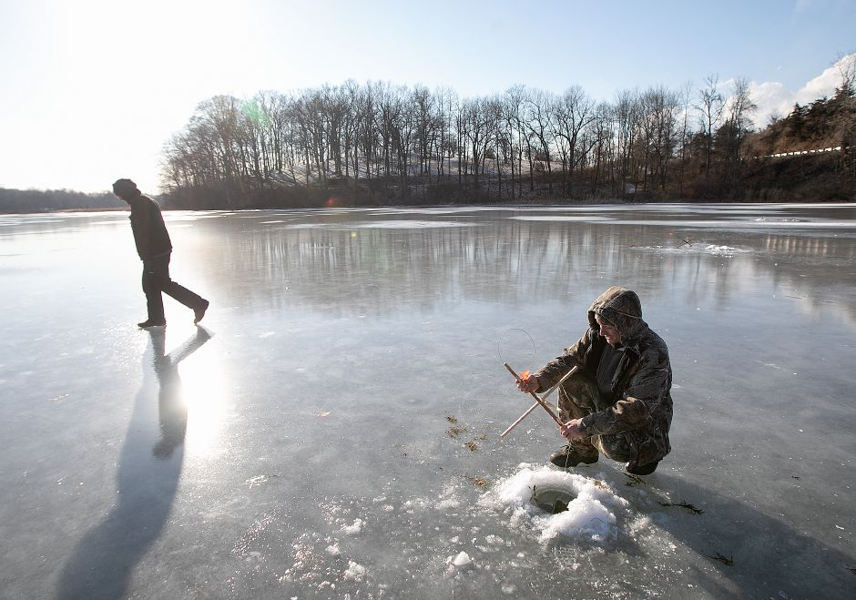 Kenny Dewey of Wallingford checks on a tip-up while ice fishing with Chris Tarasiewicz of Meriden at Black Pond in January 2019. Dave Zajac, Record-Journal