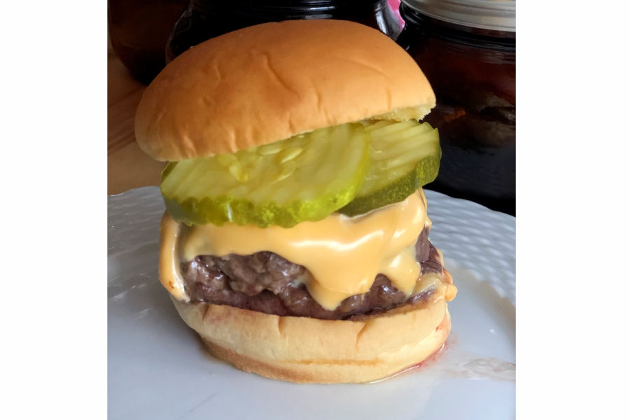 This June 2020 photo shows a cheeseburger topped with pickles in Alexandria, Va. To get the best tasting burger, try making your own blend with better quality cuts of beef. (Elizabeth Karmel via AP)