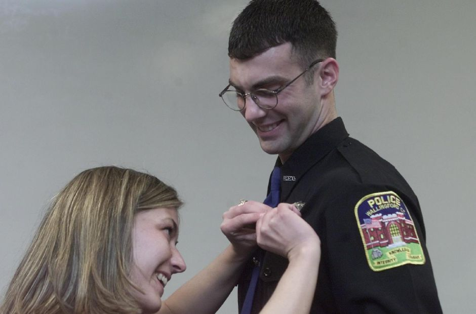 Dave Fuchs has his badge pinned on by his wife Rhonda during his swearing in ceremony at the Wallingford Police Department on Tuesday Jan. 2, 2001.