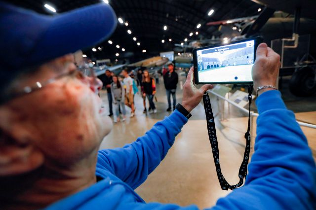In this Friday, April 26, 2019 photo, Deane Sager, of Louisville, uses a Histopad tablet to view scenes from operations on the western front of World War II at the The National Museum of the U.S. Air Force, in Dayton, Ohio. French-developed technology making its U.S. debut this month will allow new views of the D-Day invasion 75 years ago that began the liberation of France and helped end World War II. The National Museum of the U.S. Air Force near Dayton begins its D-Day commemorations...