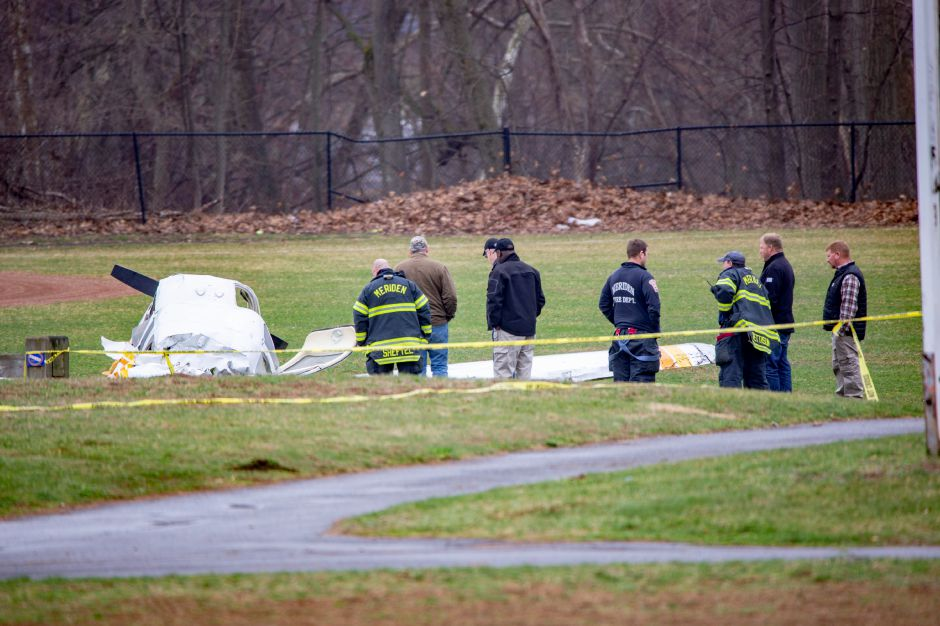 Emergency crews look over the wreckage Friday morning April 12, 2019 of a plane that crashed on the field at Wilcox Technical High School in Meriden Thursday night. | Richie Rathsack, Record-Journal