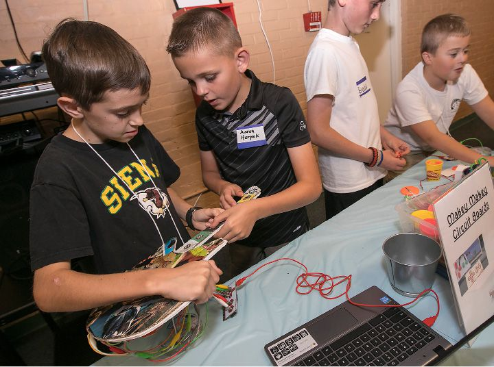 STEM participants, Jack Laffin, 11, left, and Aaron Herpok, 10, of Wallingford, try to get sounds out of a handmade guitar they wired up while showing their skills during an event where AT&T contributed 100,000 to the NEA Foundation to support CT Stem Academy at Spanish Community of Wallingford, Friday, Sept. 22, 2017. | Dave Zajac, Record-Journal
