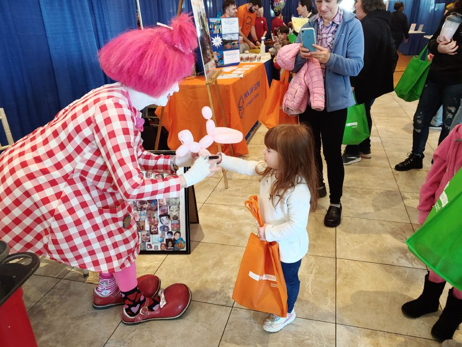 Valentine the Clown (Diana Sheard) hands a balloon animal to Natalie Adams, 4 of Plantsville Sunday. Natalie was attending the Healthy Family FunFest at the Aqua Turf.  Photo by Mary Ellen Godin