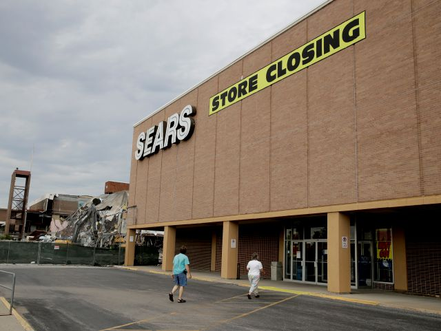 FILE- In this July 8, 2017, file photo people walk into a Sears store slated for closing that is next to a mall that is being torn down in Overland Park, Kan. Sears has filed for Chapter 11 bankruptcy protection Monday, Oct. 15, 2018, buckling under its massive debt load and staggering losses. The company once dominated the American landscape, but whether a smaller Sears can be viable remains in question. (AP Photo/Charlie Riedel, File)