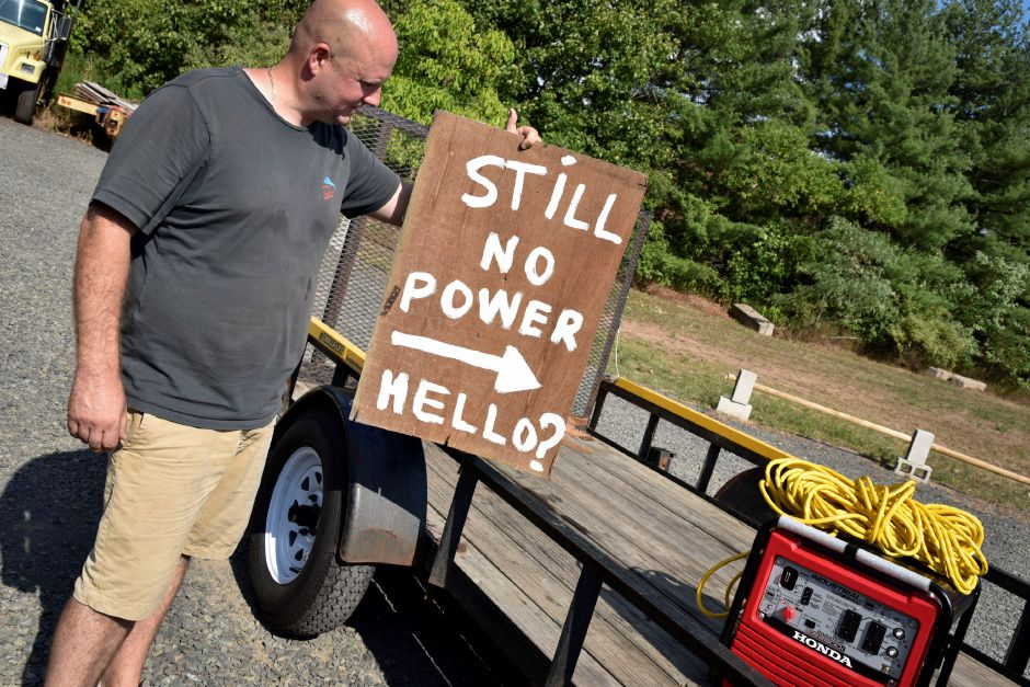 Jaime Sewell, owner of Southington PowerSports, holds up a sign on Aug. 10 that a resident in need had hung outside their home. The resident gave him the sign to remember how he helped them, by loaning a generator while power was out. | Bailey Wright, Record-Journal