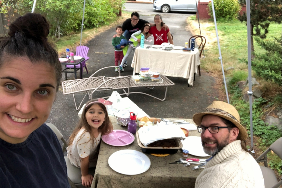 With COVID-19 making indoor dinners with friends a potential health risk, Jennifer Fliss, front left, held a socially-distanced Rosh Hashanah supper with neighbors in her Seattle driveway this year, as seen in this photo from Sept. 19, 2020. She