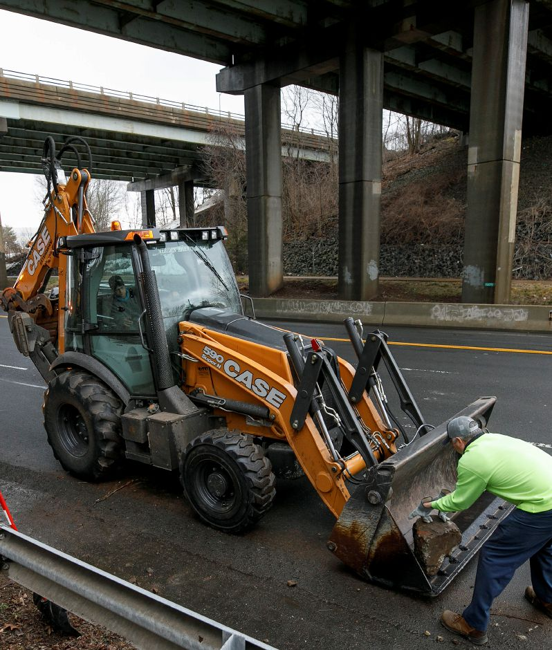 Mike Gaj, a crew leader for Meriden Public Works Highway Division, rolls a large rock into a backhoe along Lewis Avenue after an overturned dump truck lost its load on Interstate 691 eastbound in Meriden, Mon., Mar. 1, 2021. Dave Zajac, Record-Journal